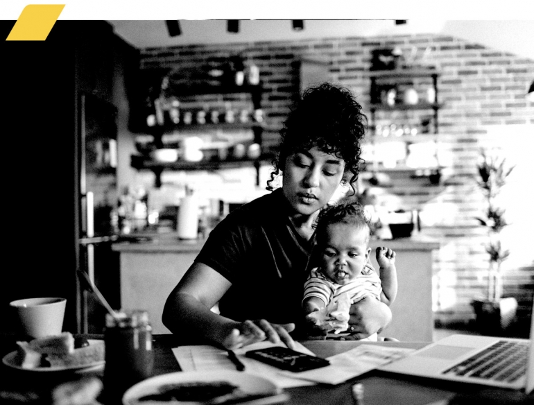 Woman holding a baby while working from home